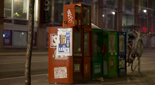 A photo of news stands that was shot in Toronto in the winter. It holds magazines such as Now and Toronto Sun