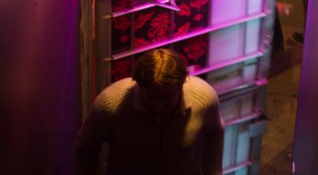 A faceless man entering a building